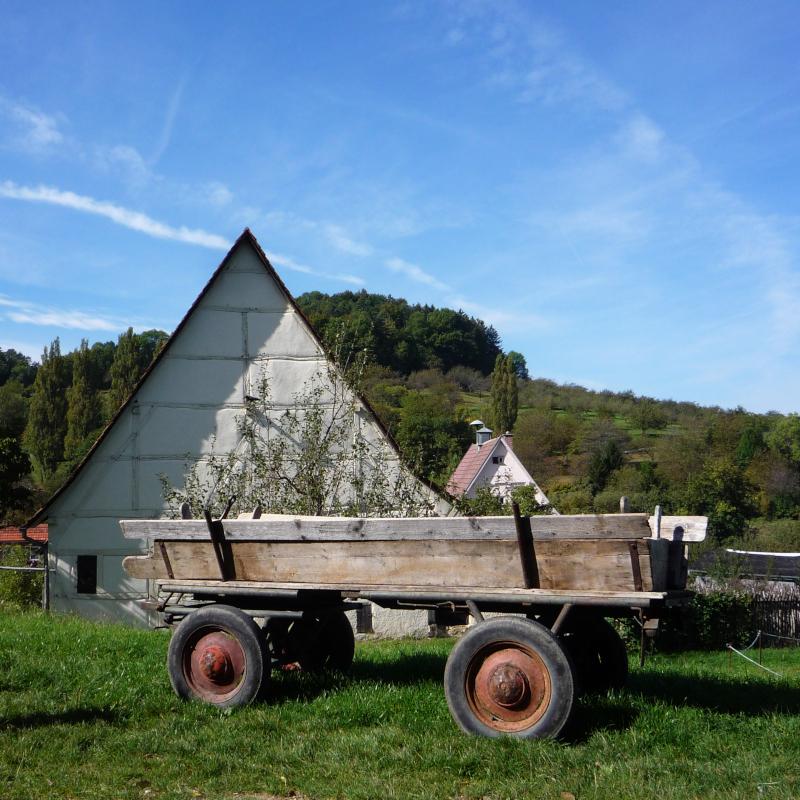 Alter Traktoranhänger vor einer alten Fachwerkscheune