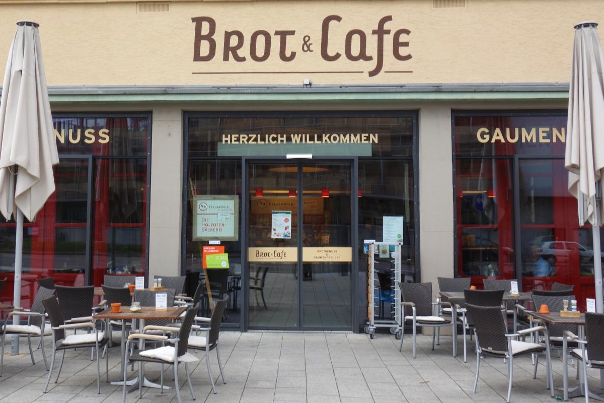 """Eingangsbereich von """"Brot und Cafe"""" mit Tischen und Stühlen im Außenbereich und einer elektrischen Eingangstür"""
