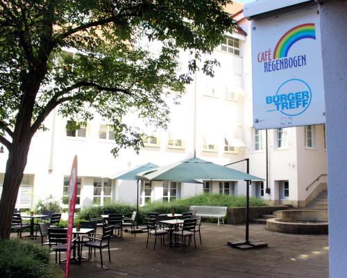 """Außenbereich des """"Café Regenbogen"""" mit mehreren Tischen"""