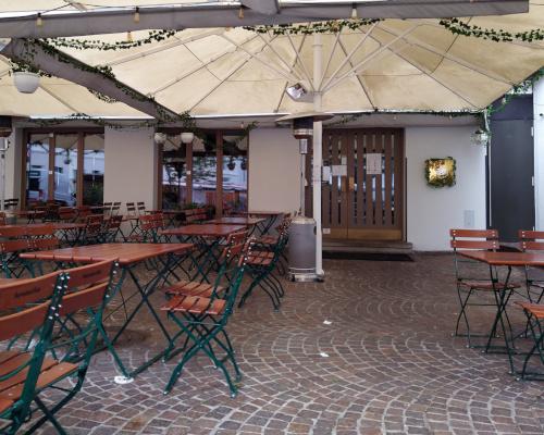Außenbereich des Restaurants Holz & Feuer mit mehreren Tischen, Stühlen unter Sonnenschirmen