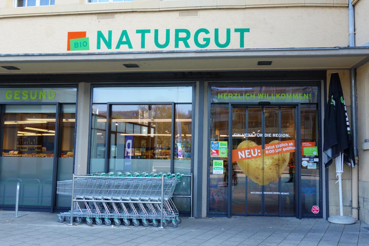 Eingang zum Biomarkt mit elektrischer Tür. Davor mehrere Einkaufwagen.