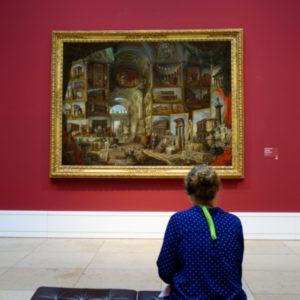 Frau, die auf einer Bank vor einem Gemälde sitzt.